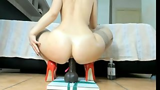 Blonde in stockings and high heels fucks a big black dildo